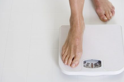 Woman Stepping onto Scale --- Image by © Royalty-Free / Corbis